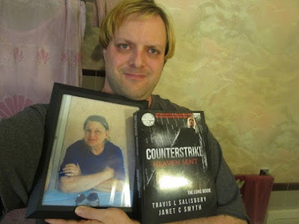 Travis L Salisbury With Counterstrike Long Book And Mother Janet-June 02 2017. Mother Janet Smiles Proudly Back At The Official Completion Of The Family Project, Some Two And A Half Years After Her Death And One Year After The New Author Rebooted It.