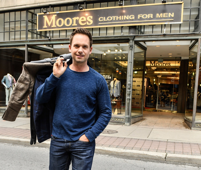 Suits star Patrick J. Adams donates suits to Moores' Toronto store for the retailers' 8th annual Canadian Suit Drive. Adams is urging Canadians to donate gently worn professional clothing at stores nationally throughout July. Donations are distributed to nearly 75 organizations that help disadvantaged men and women re-enter the workforce. Photo credit: George Pimentel