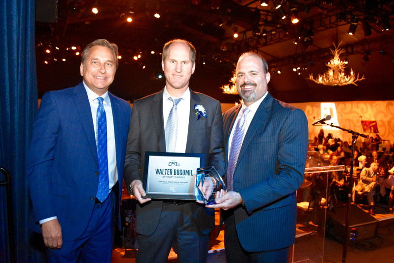 Affinity Gaming CFO Walter Bogumil (center), receives Financial Executive of the Year in Gaming/Hospitality award from KSNV anchor Dana Wagner (left) and FEI Las Vegas Chapter President Gary Vecchiarelli (right)