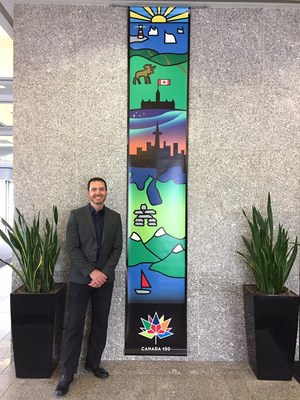 """David Hook, winner of Sakto Corporation's banner design competition in honor of Canada's 150 anniversary, stands next to his design entitled """"Coast to Coast."""" The design depicts Canada's diverse and captivating landscape in a stained glass inspired aesthetic. The banners will be displayed across Preston Square throughout the year."""