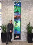 "David Hook, winner of Sakto Corporation's banner design competition in honor of Canada's 150 anniversary, stands next to his design entitled ""Coast to Coast."" The design depicts Canada's diverse and captivating landscape in a stained glass inspired aesthetic. The banners will be displayed across Preston Square throughout the year."