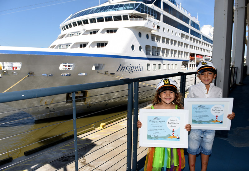 """Oceania Cruises recognizes 4-year-old Lorenna D'Amore Nogueira and her brother, 6-year-old Henrique D'Amore Nogueira, as the """"Youngest World Cruisers"""" in front of m/s Insignia while docked in New York, Wednesday, June 28, 2017, during its 180-day Around the World sailing. (Photo by Diane Bondareff/AP Images for Oceania Cruises)"""