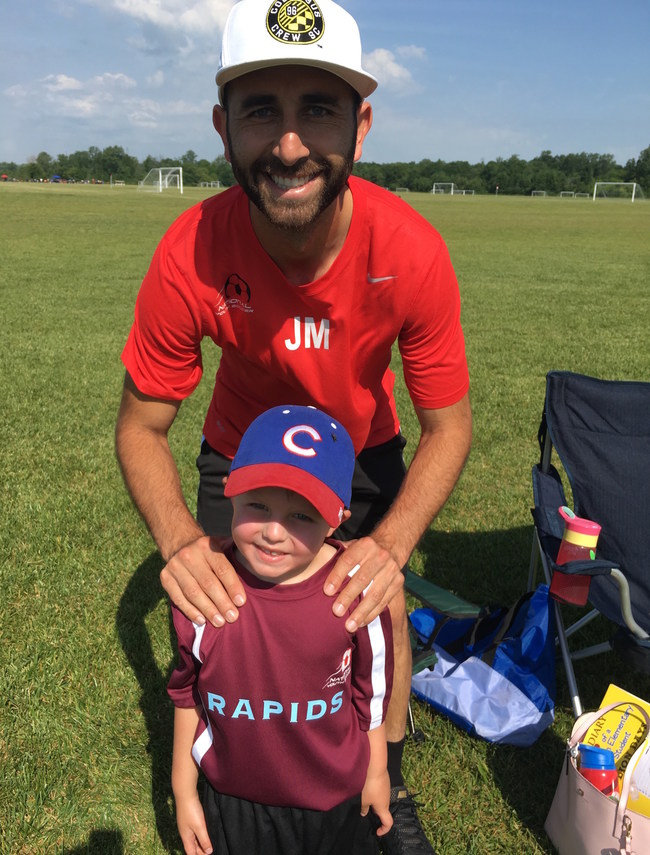 Justin Meram is all smiles with the children playing soccer.