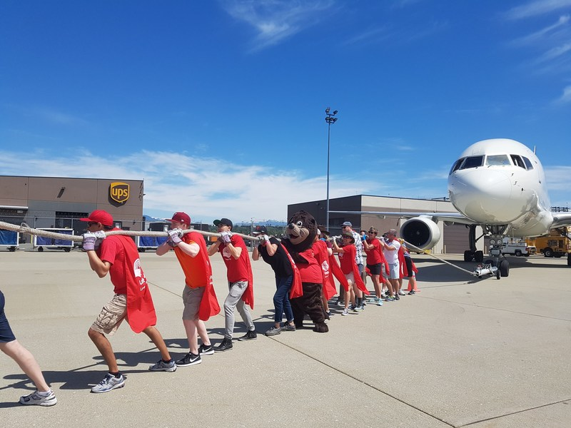 """On June 25, 2017, UPS Canada hosted its 4th """"Pulling For U"""" plane pull in Vancouver in support of United Way of the Lower Mainland, raising more than $34,000. Teams of 15 competed to pull a 127,000 lb UPS """"Brown Tail"""" airplane, 50 ft. across the tarmac in the shortest amount of time. Collectively, the UPS Canada """"Pulling For U"""" plane pulls for United Way of the Lower Mainland have raised over $125,000. Since 2011, """"Pulling For U"""" plane pull events have raised over $530,000 for United Way across Canada. (CNW Group/UPS Canada Ltd.)"""