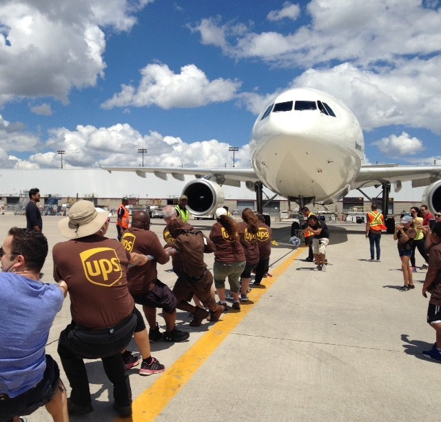 """On June 24, 2017, UPS Canada hosted its 2nd """"Pulling For U"""" plane pull in Mississauga in support of United Way Peel Region. Teams of 15 competed to pull a 200,000 lb UPS """"Brown Tail"""" airplane, 50 ft. across the tarmac in the shortest amount of time. Collectively, the UPS Canada """"Pulling For U"""" plane pulls for United Way Peel Region have raised over $13,500. Since 2011, """"Pulling For U"""" plane pull events have raised over $530,000 for United Way across Canada. (CNW Group/UPS Canada Ltd.)"""