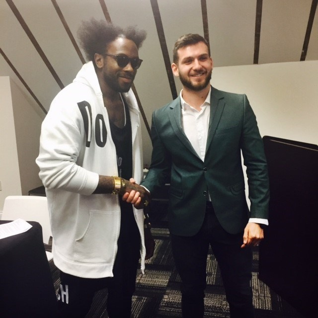 Saint Louis Fashion Incubator designer Charles Smith II of Smith II (left) shakes Grandmaster Cristian Chirila's hand (right) at a visit to the Saint Louis Chess Campus in 2016. This duo is one of several collaborating to create the first chess uniform through the Pinned! Designer Chess Challenge. The winning design will be revealed on August 1, 2017 during the opening ceremonies for the prestigious, international chess tournament, the Sinquefield Cup.