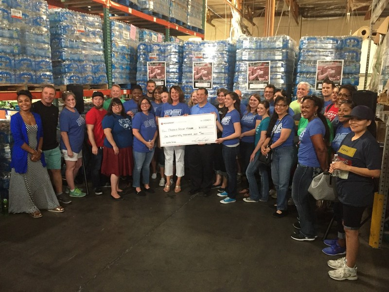 Movement Mortgage team members present a check for $150,000 in addition to donating 400,000 bottles of water to the Phoenix Rescue Mission's Code Red campaign.