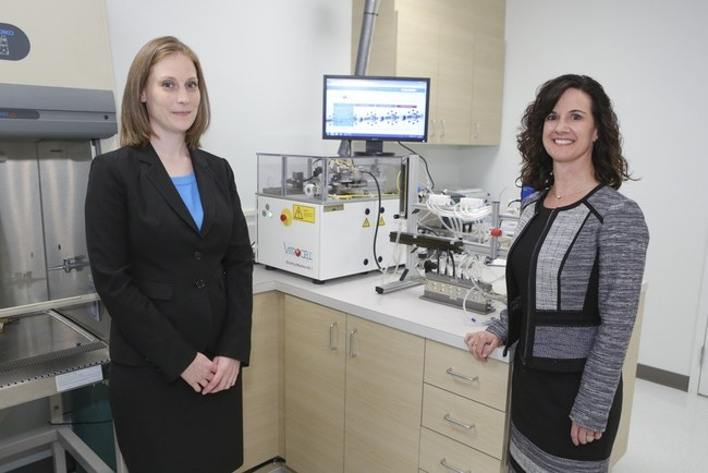 Amy Clippinger of PISC and IIVS President, Erin Hill, unveiling the new VITROCELL System, which was generously donated by PISC. (PRNewsfoto/IIVS)