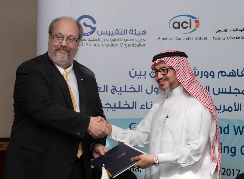 Ronald G. Burg, Executive Vice President of the American Concrete Institute, and Dr. Nabil bin Ameen Molla, Secretary General of the GCC Standardization Organization, agreeing to use of ACI 318, ACI 301, and more, in the Gulf Building Code.