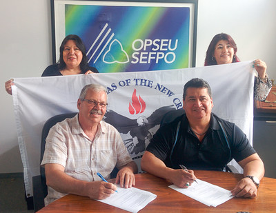 OPSEU President Warren (Smokey) Thomas (left) and Mississaugas of the New Credit Chief R. Stacey Laforme sign a Memorandum of Understanding with members of the Indigenous Mobilizing Team. (CNW Group/Ontario Public Service Employees Union (OPSEU))