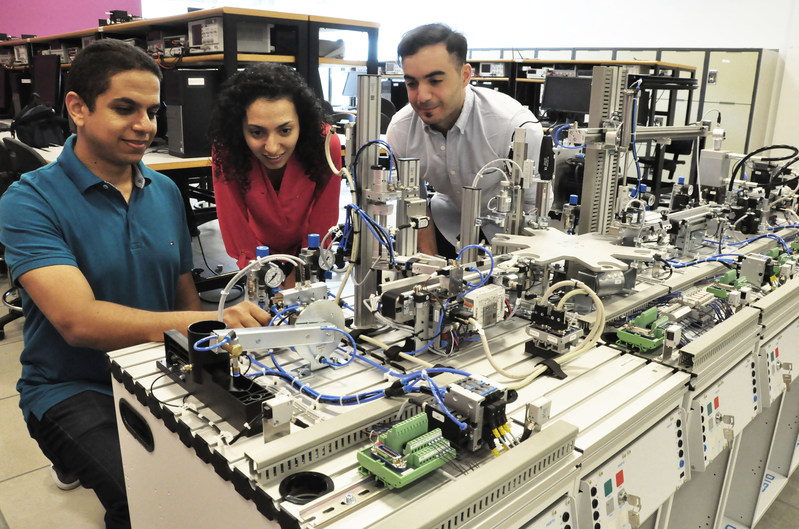 Simon Fraser University Instructor Amr Marzouk shows new state-of-the-art industrial training assembly line equipment to SFU mechatronics students Anahita Mahmoodi and Mouataz Kaddoura. Both are enrolled in the Siemens Mechatronics Systems Certification Program that starts in August 2017. (CNW Group/Siemens Canada Limited)