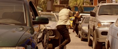 ANGEL (Kevin Gage, right) and TURK (Paul Sidhu, right) in a shootout on a crowded street in Mexico.