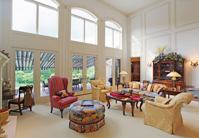 The home's grand salon offers two-story ceilings and large windows presenting views of the verdant surroundings. Learn more at PennLuxuryAuction.com.