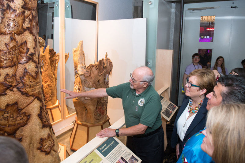 Tom Gallagher, President, Ontario Wood Carvers Association, details the artistry of The Maple Leaf Forever Tree, an eight-foot, hand-carved sculpture that depicts Toronto's history, unveiled at the Ontario Science Centre today. L-R: Minister of Tourism, Culture and Sport Eleanor McMahon, Chief R. Stacey LaForme, Mississaugas of the New Credit First Nation, and Chief Laurie Carr, Hiawatha First Nation (CNW Group/Ontario Science Centre)