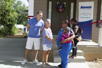 Retired NFL quarterback Kurt Warner and his wife Brenda greet new St. Louis homeowner Kamerial and her children before a surprise unveiling of a home full of furniture donated by Aaron's, Inc. and its divisions Aaron's and Progressive Leasing.  The awarded home was a result of a partnership of Aaron's, U-Haul, Habitat for Humanity Saint Louis, and Kurt Warner and his wife Brenda's First Things First Foundation (FTFF).