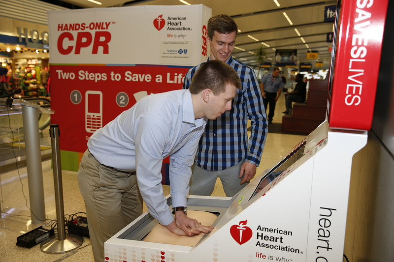 Cardiac arrest survivor Sean Ferguson practices Hands-Only CPR on a training kiosk at Indianapolis International Airport in 2016 with friend Matt Lickenbrock. Lickenbrock learned Hands-Only CPR at the training kiosk at DFW International Airport in April 2015. Days later, he performed Hands-Only CPR on Ferguson after he was struck by lightning in a parking lot at the University of Dayton.