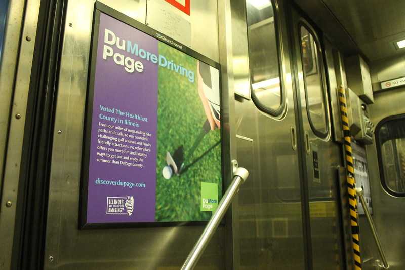 The new branding initiative includes Metra posters that emphasize DuPage County's green spaces.