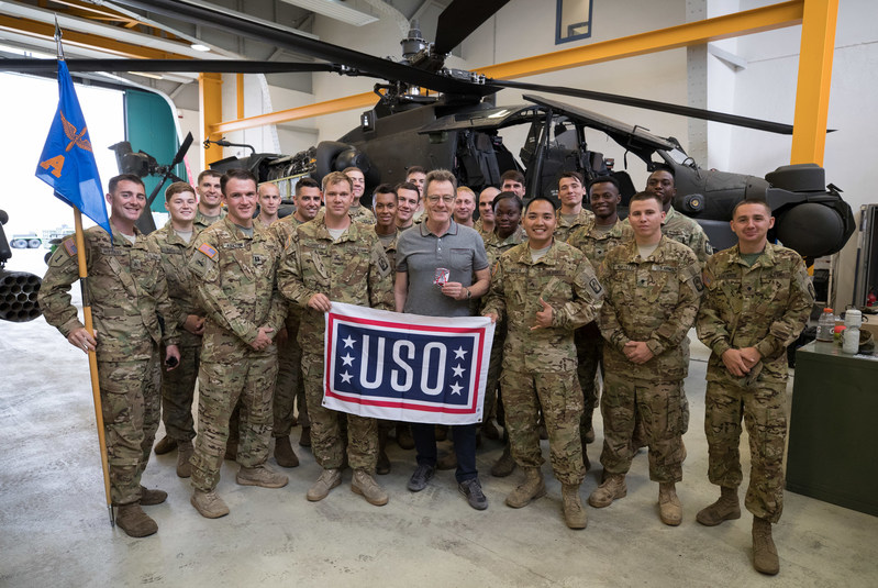 Actor Bryan Cranston (center in grey shirt) poses for a photo with service members in front of a Cobra attack helicopter during a USO tour stop at Katterbach Kaserne in Germany on July 24, 2017. Cranston is visiting servicemen and women as part of a week-long USO tour to Germany and the United Kingdom. USO Photo by Fred Greaves