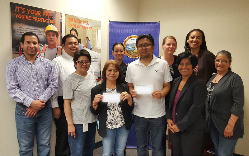 Labor Commissioner's Office staff in Oakland with residential caregivers Lourdes Reginio and Alquin Santillan (holding checks, front row center). Also pictured to their right is Hina Shah, Women's Employment Rights Clinic, Golden Gate University School of Law.