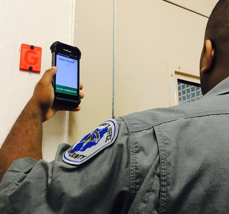 Corrections officer logging security checks using SPARTAN, an ultra-rugged Android device from GUARDIAN RFID.