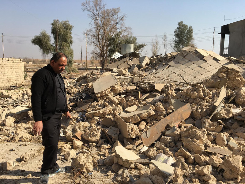A Catholic church ruined by ISIS in Karamdes, Iraq, is examined by a priest following the predominately Christian town's liberation.