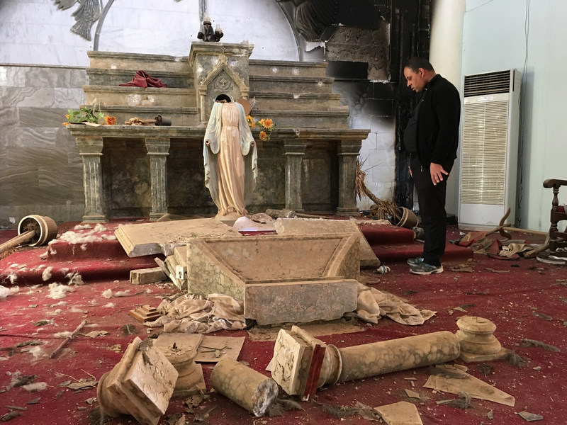 A priest examines the ruins, including a decapitated statue of Mary, in the Catholic church in Karamdes, Iraq, following the town's liberation from ISIS.