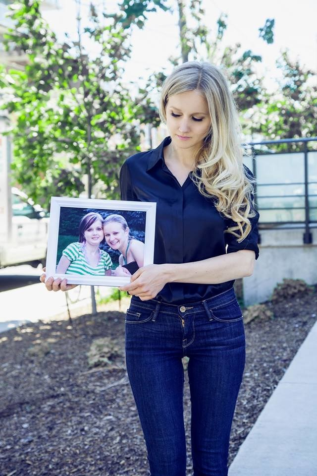 Entrepreneur and creator of JWLS, holds a photo of herself and late sister Julia Lyons, the inspiration for the brand.