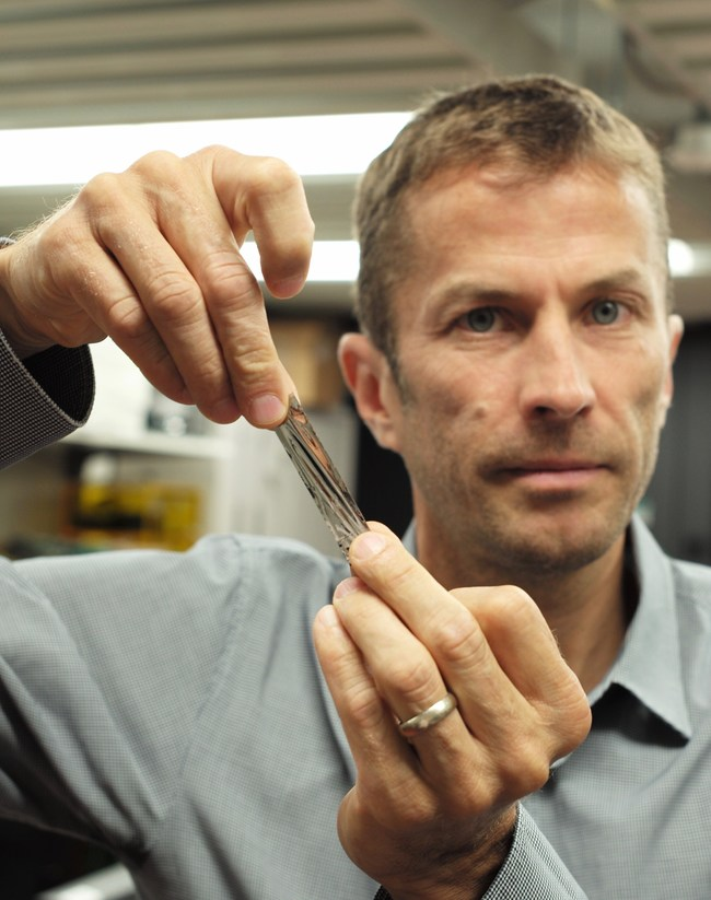 IBM Research scientists have achieved a new world record in tape storage – their fifth since 2006. The new record of 201 Gb/in2 (gigabits per square inch) in areal density was achieved on a prototype sputtered magnetic tape developed by Sony Storage Media Solutions.     In this photo, IBM scientist Dr. Mark Lantz, holds a one square inch piece of Sony Storage Media Solutions sputtered tape, which can hold 201 Gigabytes, a new world record.      Photo credit: IBM Research