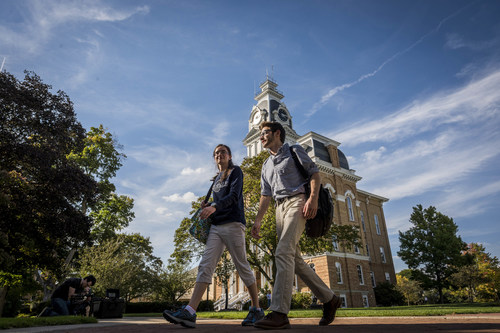 Students walk past Central Hall on the campus of Hillsdale College.