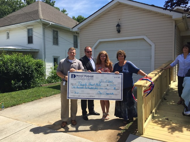 Receiving a check from Dover Federal Credit Union for materials to build a ramp for a WWII Veteran. The ramp was constructed by the Home Builders Association of Delaware Photo (l-r) Tyler Kuhn, Community Relations Officer, Chaz Rzewnicki, President and CEO of Dover Federal Credit Union; Sue Yocum, Community Relations officer; Vicki Thomas, Purple Heart Homes