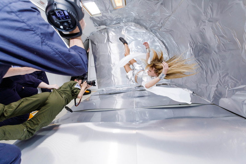 Photographer Reiko Wakai is held in position while shooting model Stav Strashko during a zero gravity photo shoot for Wix's Capture Your Dream Photo campaign. Source: Steve Boxell – ZERO-G