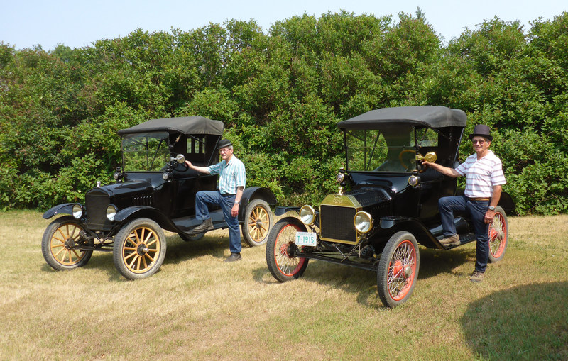 Brothers Bill (left) and Jim (right) Ewert with two of their Model T Roadsters, selling on August 19 in Drake, SK. (CNW Group/Ritchie Bros.)