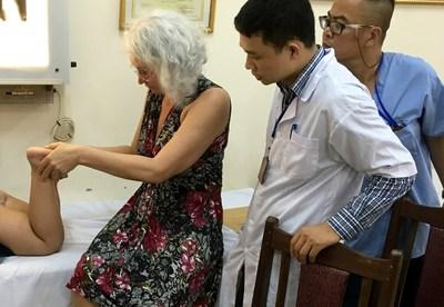 AOFAS volunteer surgeon Isabella V. van Dalen, MD, PhD, examines a patient at the Ba Vi Orthopedics Rehab Center in Ba Vi, Vietnam, as local surgeons observe.