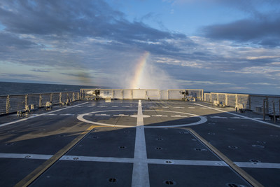 """A rainbow is visible in LCS 9's """"rooster tail"""" during Builder's Sea Trials on Lake Michigan. At top speed, LCS 9's four water jets move approximately 2 million gallons of water per minute producing a 30-foot wall of water known as a rooster tail. That's enough water to fill an Olympic swimming pool in 20 seconds."""