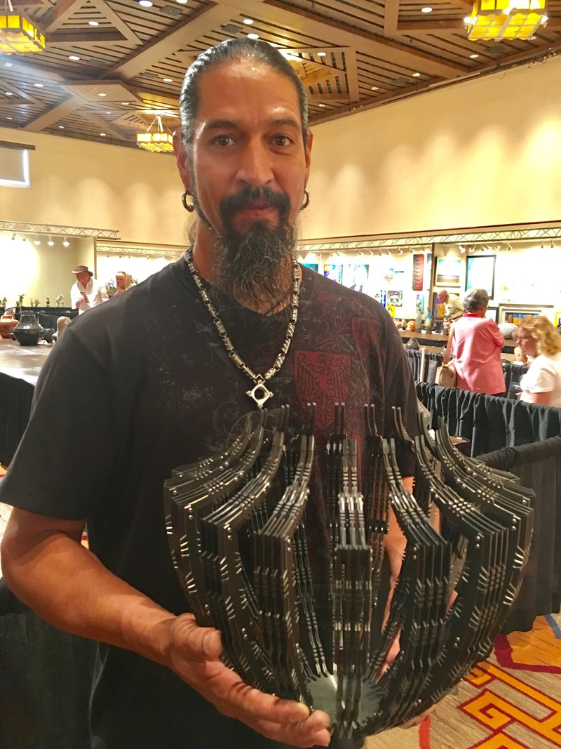 """Pat Pruitt (Laguna Pueblo), 2017 Best of Show winner at Santa Fe Indian Market, with his winning piece. """"Sentinel v1.0"""" was entered into the sculpture classification; it is made of zirconium and titanium. The 96th Santa Fe Indian Market, presented by the Southwestern Association for Indian Arts (SWAIA) is held on August 19 and 20."""