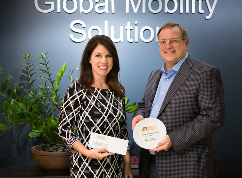"""Lisa Notaro, Chief Development and Communications Officer for St. Mary's Food Bank Alliance, presents Steven Wester, President of Global Mobility Solutions, with the """"Hunger Hero"""" award."""