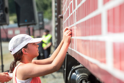 A girl places a dream for Canada on the Spirit of Tomorrow car. (CNW Group/Canadian Pacific)