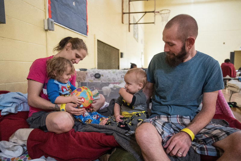 Shelby and Nick play with their children, 2-year-old Sarah*, and 1-year-old Aaron* on their cot in a shelter in San Antonio, Texas, on August, 27, 2017. The family has been in the shelter now for four nights. They evacuated from Rockport where Hurricane Harvey made land fall. They have lost everything. Save the Children distributed a variety of baby items to shelters in the San Antonio area, including the cribs for Sarah* and Aaron*. *Names changed. Photo Credit: Susan Warner/Save the Children