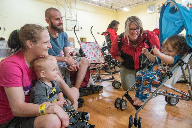 Sarah*,2, tries out a new stroller donated by Save the Children as staff member Caroline Haas looks on. Sarah's* family including mom Shelby, dad Nick and brother Aaron*,1, has been in the shelter now for four nights. They evacuated from Rockport where Hurricane Harvey made land fall. They have lost everything. Save the Children distributed a variety of baby items to shelters in the San Antonio area, including cribs for the family. *Names changed. Photo Credit: Susan Warner/Save the Children