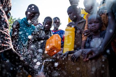 Des personnes déplacées internes remplissent des contenants à un point d'eau du camp Dalori, à Maiduguri, dans l'État de Borno, au Nigeria. ©UNICEF/UN055942/Ashley Gilbertson (Groupe CNW/UNICEF Canada)