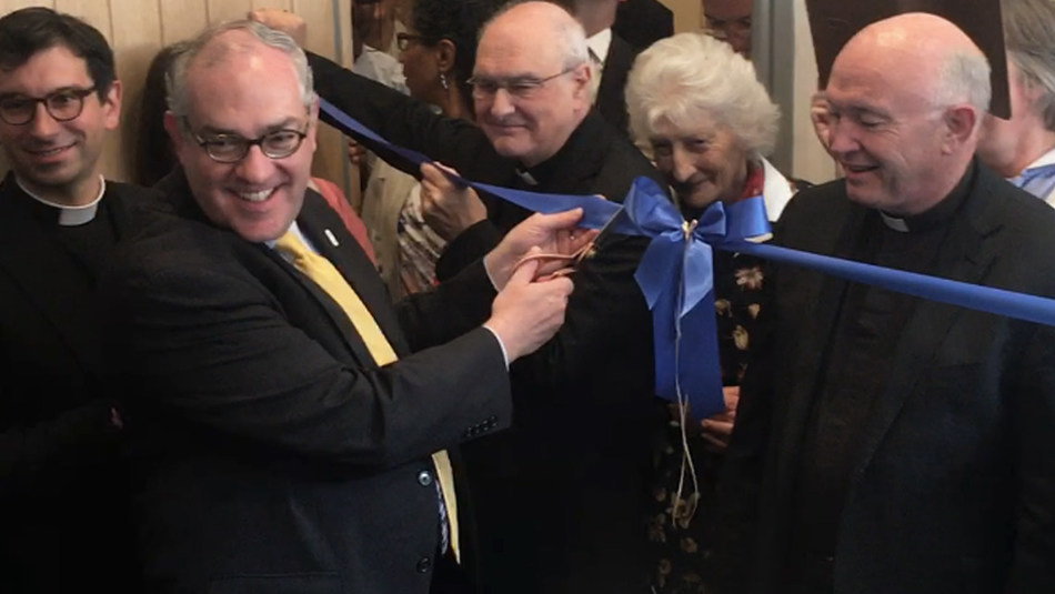 EWTN Chairman and Chief Executive Officer Michael P. Warsaw cuts a ceremonial ribbon at the dedication of EWTN's first studio and office in the United Kingdom. The Most. Rev. Alan Hopes, Bishop of East Anglia (center), and Monsignor John Armitage, Rector of the Shrine of Our Lady of Walsingham (right), look on. (Photo credit: EWTN/Alan Holdren)