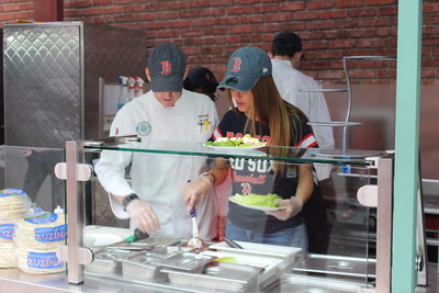 """Red Sox fan, Emmy winning host and best-selling author, Maria Menounos, works with Aramark Senior Executive Chef, Ron Abell, behind her new stand at Fenway Park, """"Maria's Greek Kitchen"""", which features her family's recipes and organic ingredients."""