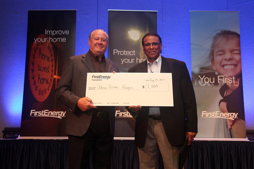 FirstEnergy President and Chief Executive Officer Charles Jones, left, presents a check to former Cleveland Indians star Andre Thornton on behalf of the Akron Urban League as part of FirstEnergy's recent semi-annual staff meeting in Akron. Thornton spoke to more than 250 members of FirstEnergy's leadership team about his experiences as a minority business owner once his baseball playing career ended.