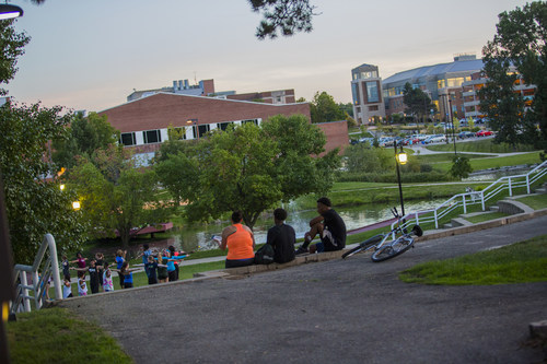 Twilight on the EMU campus shows Halle Library to the right, Bowen Field House at center and the Lakehouse Amphitheater and ponds in the foreground.