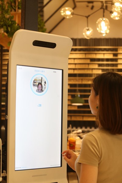 """A customer paying using Alipay's new """"Smile to Pay"""" facial recognition payment solution in KPRO, Hangzhou"""