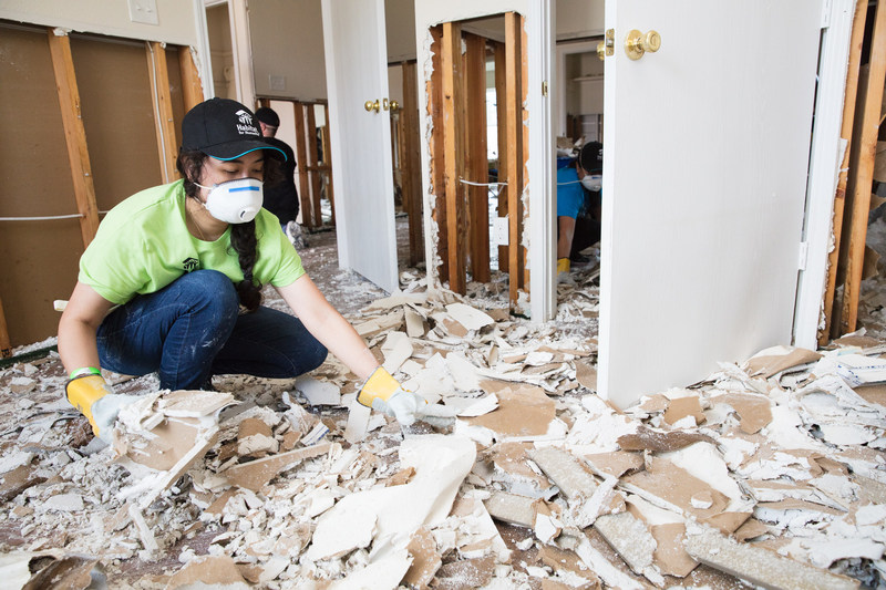 Habitat for Humanity volunteer Mali Mahnee helps clean out homes flooded by Hurricane Harvey in northeast Houston in preparation for repairs.