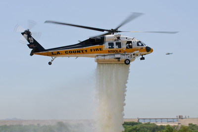 A L.A. County Sikorsky S-70 Firehawk helicopter demonstrates water suppression during a 2013 airshow. Photo credit: Trent Bell