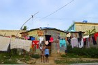 A family stands outside their home in the Dominican Republic. Homes like this one are unlikely to be able to withstand the force of Hurricane Irma. (CNW Group/World Vision Canada)