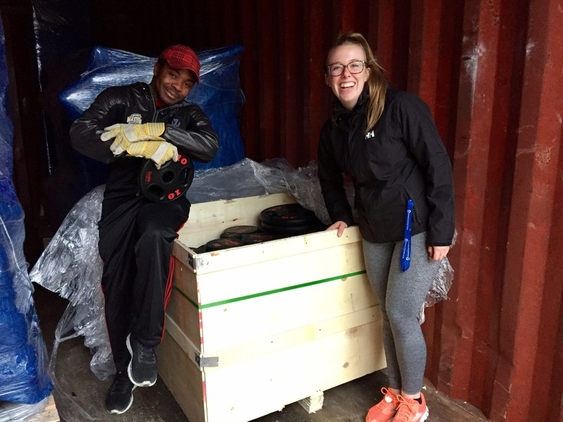 Tino Mbara and Kristyn Fanstone, volunteers with the Cambridge Bay Weight Room User Group Committee, unload a crate filled with barbell plates to set up their newly expanded fitness facility. The barbell plates are part of the $40K in fitness equipment GoodLife Fitness donated to the Hamlet of Cambridge Bay. (CNW Group/GoodLife Fitness)