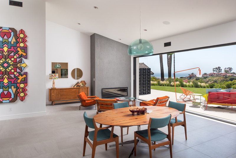 The extraordinary high ceilings and volume contributes to its welcome feeling. The public areas of the house, such as the kitchen, dining, living, and entertaining areas open up towards the backyard with sit-down white-water ocean views beyond. The main living wall disappears with the use of La Cantina pocket door, creating an 18' foot-wide opening. The front door entry is also La Cantina pocket door and allows for ocean breezes to flow through the home.